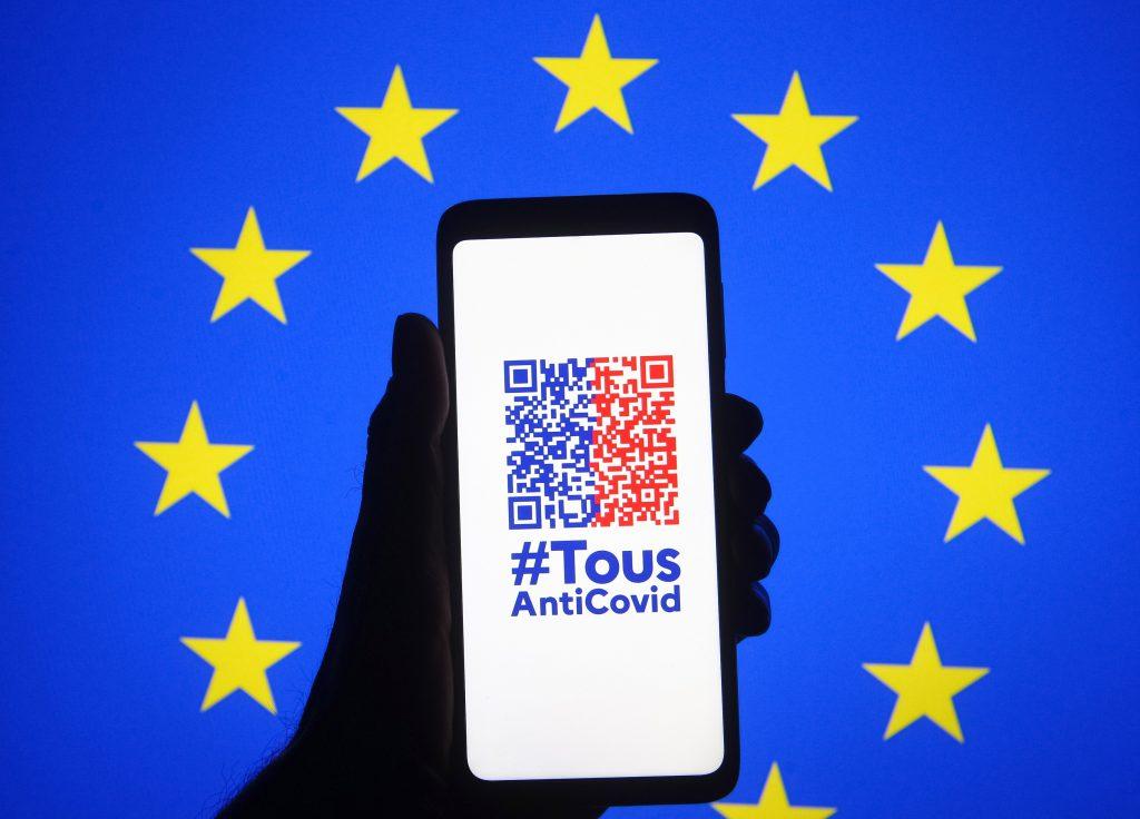EUの旗をバックに「TousAntiCovid」アプリの映し出されたスマホが掲げられている。 画像引用:https://news.artnet.com/