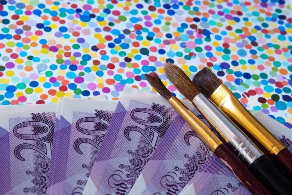 ダミアン・ハーストの作品≪The Currency≫に絵筆と紙幣が重ねられている。