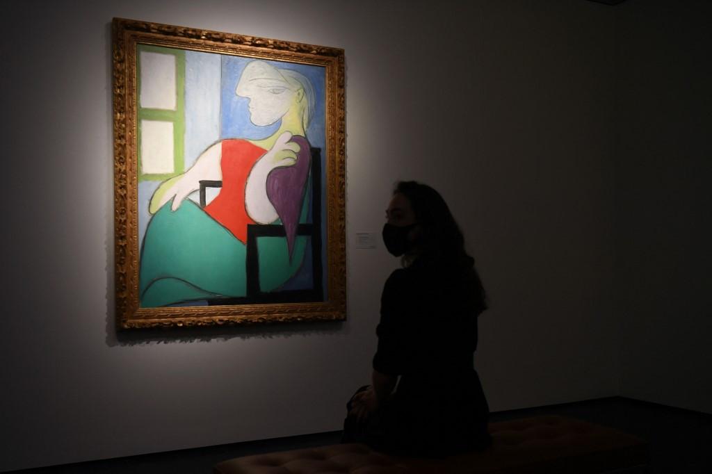 パブロ・ピカソの≪Femme assise près d'une fenêtre (Marie-Thérèse)≫の前に女性が立っている